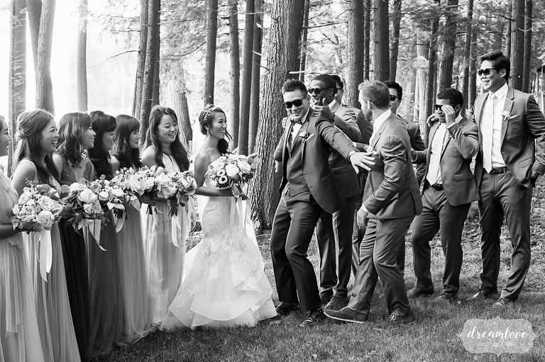Funny wedding photography of the groom pretending to hold groomsmen back from his bride in Wolfeboro, NH.