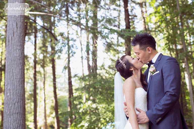 Romantic wedding photography of the bride and groom kissing in the forest in NH.