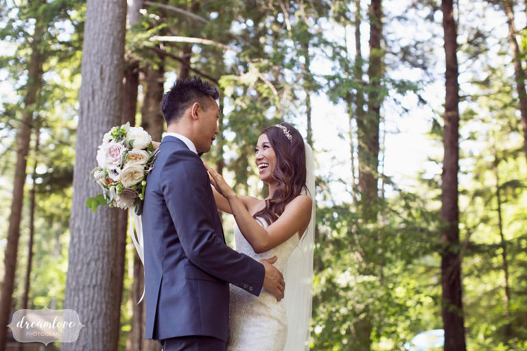 Nature style wedding photography of the bride laughing at the groom surrounded by pine trees in Wolfeboro.