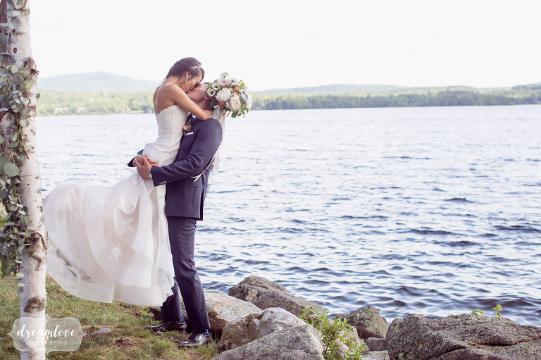 Romantic and dreamy wedding photo of the groom picking up the bride on the the shore of the lake in Wolfeboro, NH.