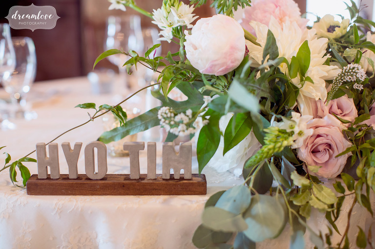 This modern wedding table decor used concrete and wood to spell the couples name at the sweetheart table at the Inn on Main in NH.