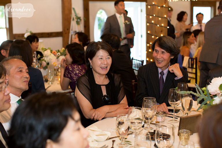 Candid wedding photography of guests laughing during cocktail hour at the Inn on Main.