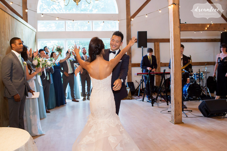 Documentary wedding photo of the bride throwing her arms around the groom before their first dance at this rustic wedding reception in Wolfeboro.
