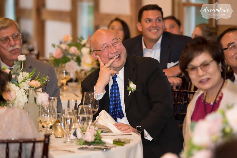 The father of the groom smiles while listening to toasts at the Inn on Main in Wolfeboro.