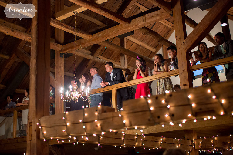 Guests listen to toasts while standing on the balcony at the Inn on Main wedding reception venue in Wolfeboro.