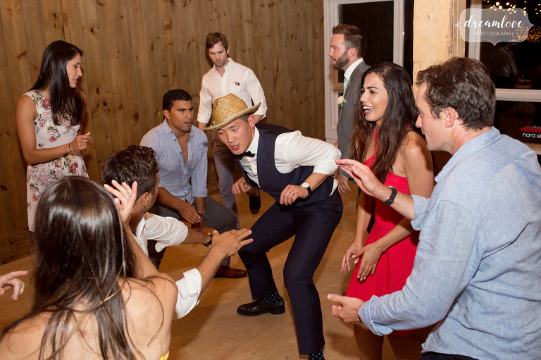 Funny photo of the groom dancing with a straw hat at the Inn on Main in Wolfeboro, NH.