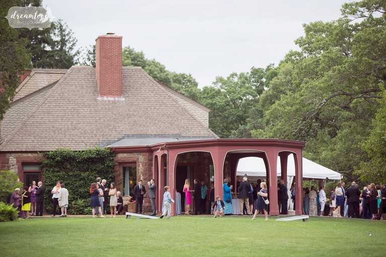 Guests enjoy the outdoor cocktail hour on the veranda at this Moraine Estate wedding in MA.