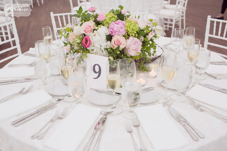 Budget friendly garden wedding centerpieces with flowers and paper table numbers.