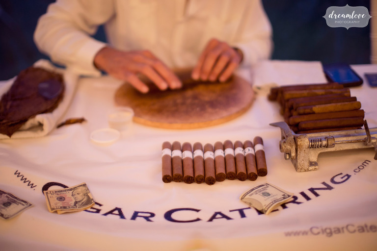 A man hand rolls cigars at the Moraine Farm estate in MA.