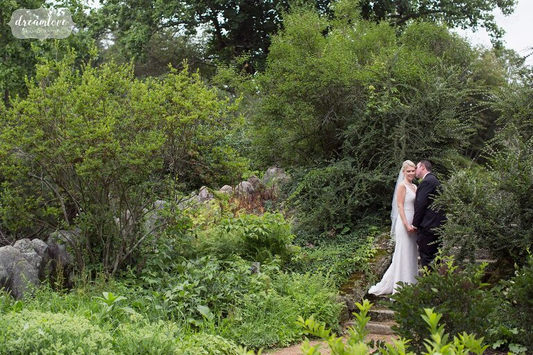 Bride and groom stand in the garden at the Moraine Farm Estate in Beverly, MA for their wedding.