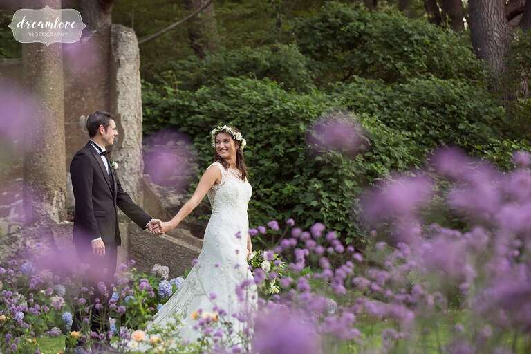 The bride leads the groom through a garden at their north shore estate wedding at Crane Estate in MA.
