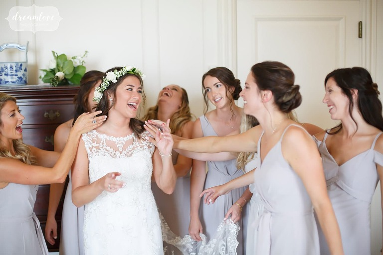 The bride is surrounded by smiling bridesmaids while getting ready at the Crane Estate in MA.