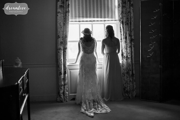Black and white photo of the bride with her bridesmaid looking out the window at the Crane Estate in Ipswich, MA.