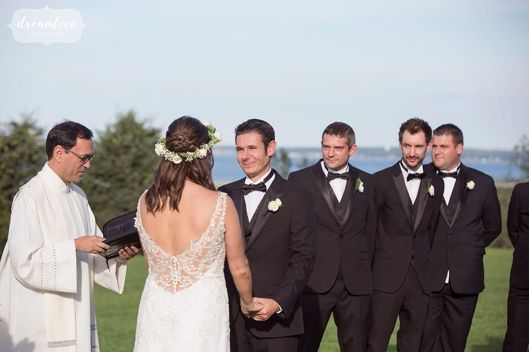 The groom smiles at the bride with the Atlantic Ocean in the background at this wedding on Castle Hill in MA.