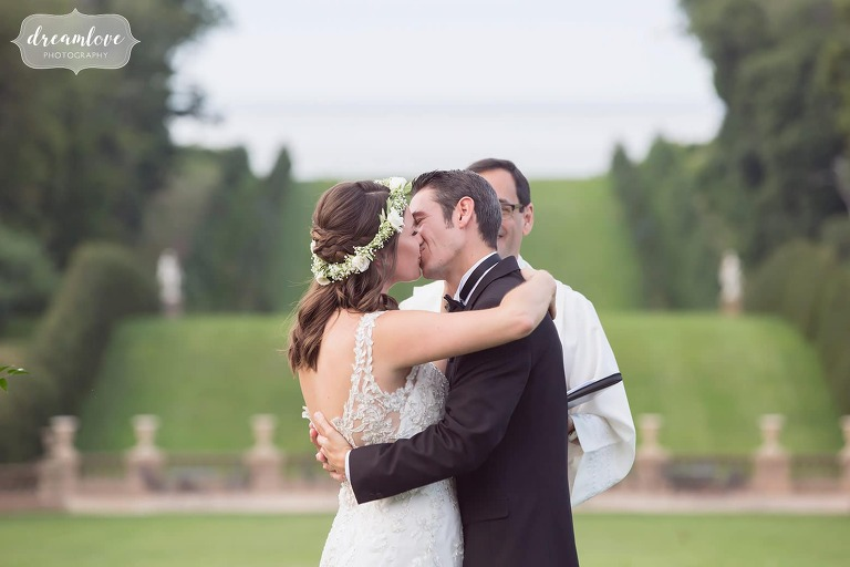 The bride and groom kiss with the rolling green lawn behind them at this north shore estate wedding in MA.