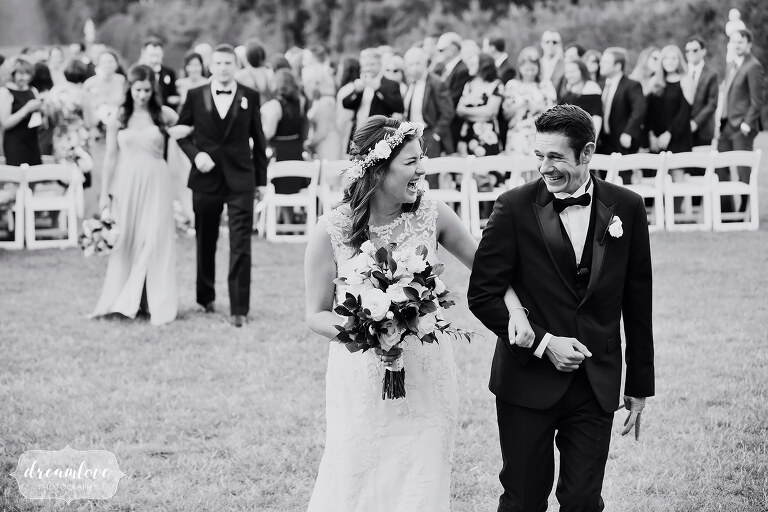 Fine art black and white wedding photo of the bride and groom exiting their ceremony at the Crane Estate.