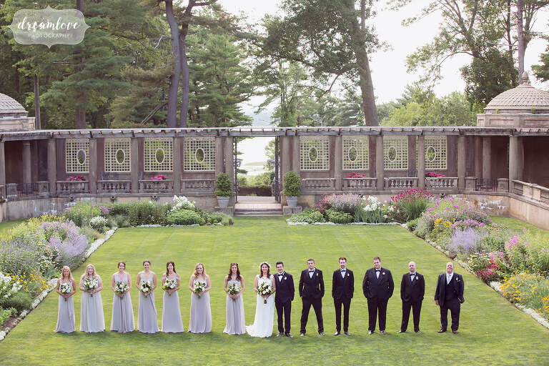 Large wedding party with lilac dresses lined up in the Italian Garden at the Crane Estate.