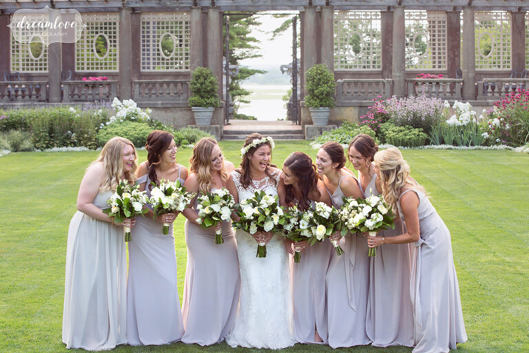 Bride surrounded by bridesmaids in lilac pastel dresses with white flowers at the Crane Estate.