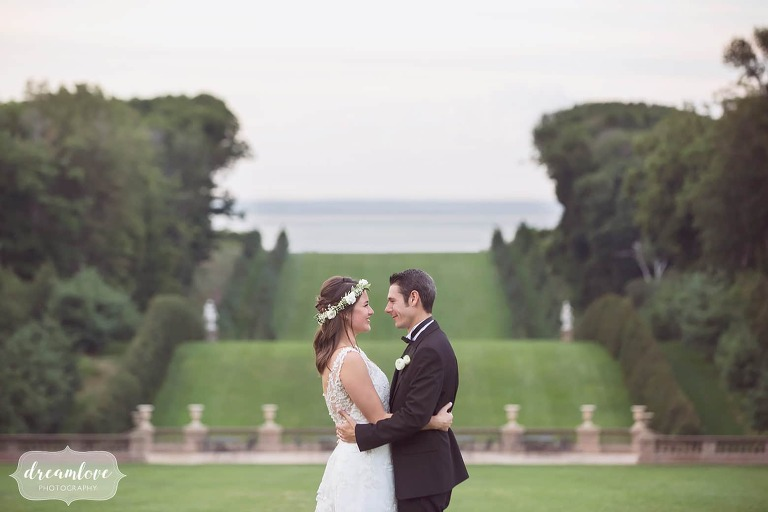 Bride and groom pose in front of the scenic lawn to the ocean at the most romantic wedding venue on the north shore of MA.