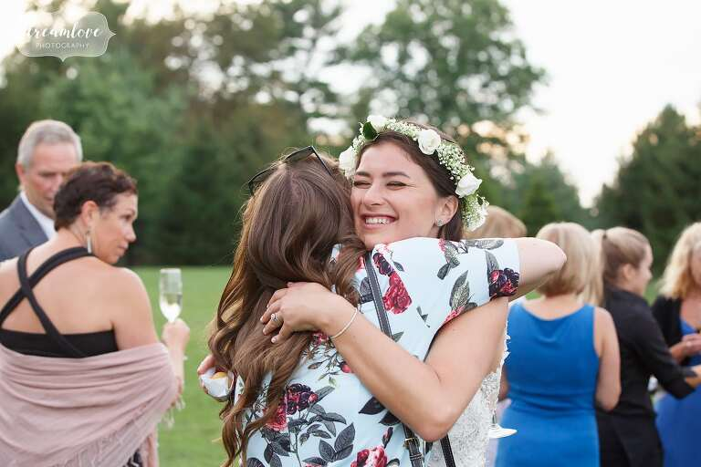 The bride hugs an old friend in this candid photo at the Crane Estate.