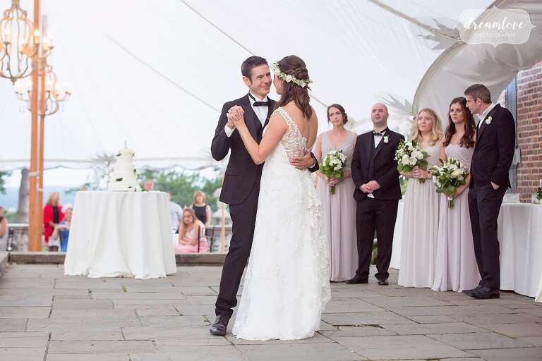 The bride and groom have their first dance under the tent at the Crane Estate venue.