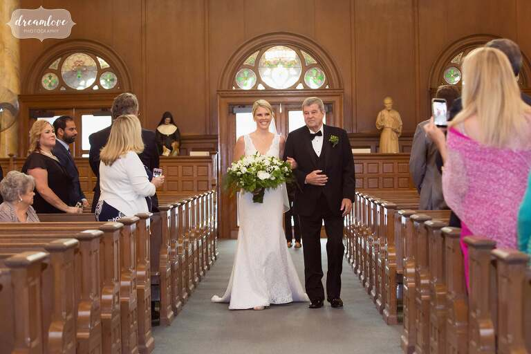 The bride and her father walk down the aisle at the St. Mary Star of the Sea church in Beverly, MA.