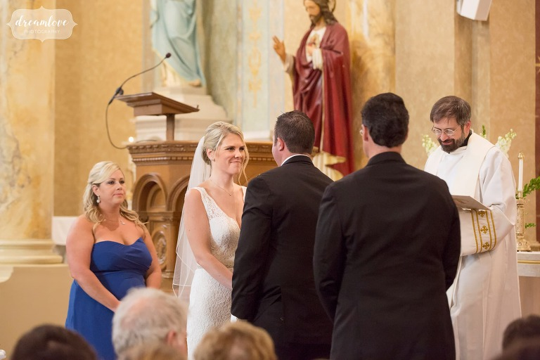 Bride looks at groom during the vows at the St. Mary church in Beverly, MA.