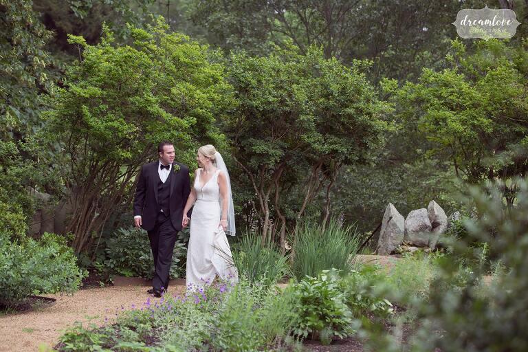 The bride and groom walk through the english garden at the Moraine Farm Estate during their wedding.