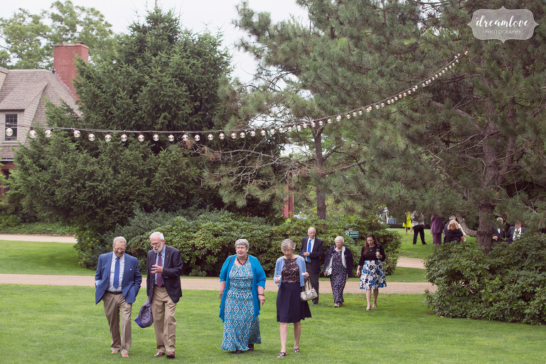 Wedding guests walk into the tent at the Moraine Farm under string cafe lights in the trees.
