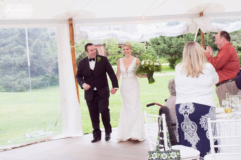 The bride and groom are introduced into the bright tent at the Moraine Farm for their wedding reception.