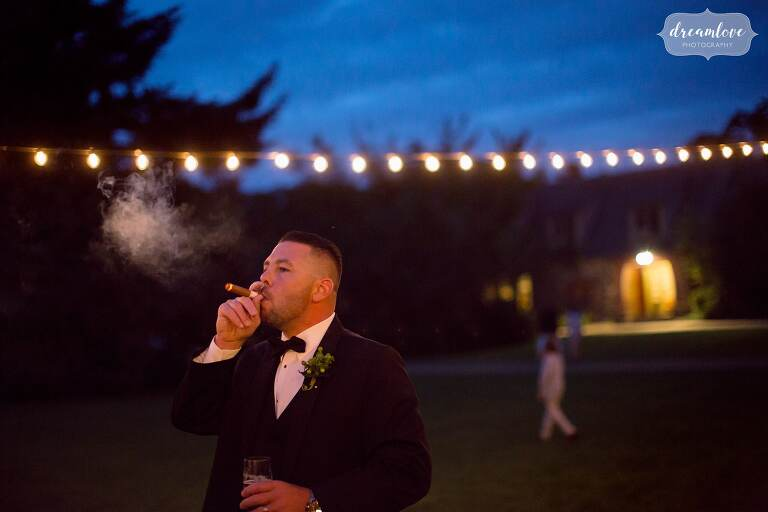 The best man puffs on a cigar under string lights at dusk at the Moraine Farm Estate.