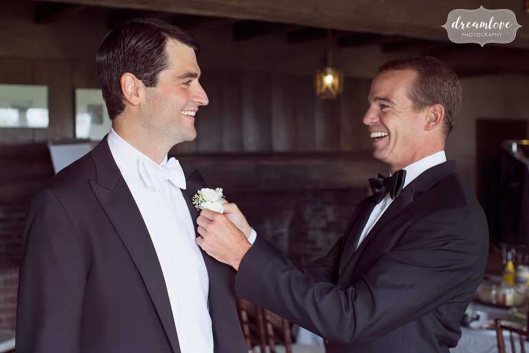 Groom's best man helps him put on his bouttoneiere at the Inn at Castle Hill in MA.