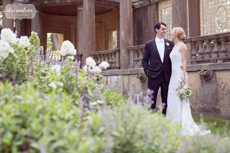 The bride and groom pose in the flower garden at the Crane Estate.