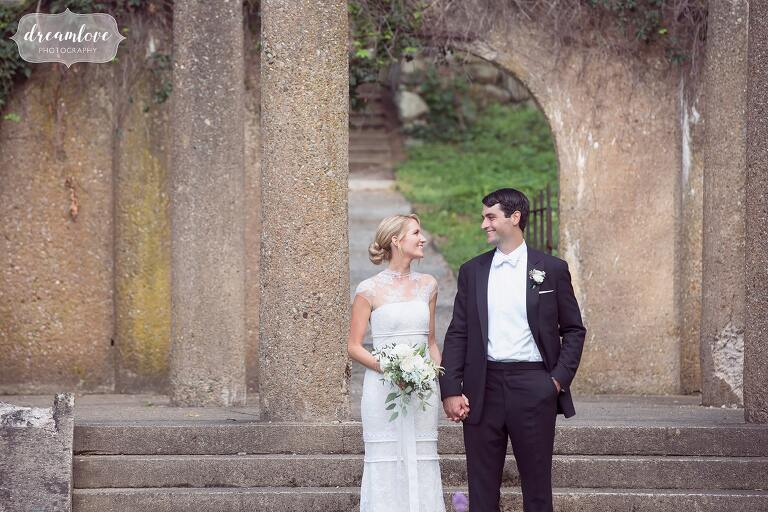 Bride and groom pose in an ancient ruins garden at the Crane Estate for their wedding on the north shore of MA.