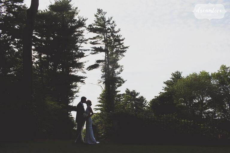 A unique photo of the bride and groom surrounded by tall pine trees at the Crane Estate.