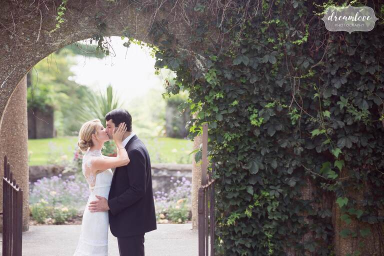 The bride and groom have a romantic kiss under an arch covered in ivy at the Crane Estate.