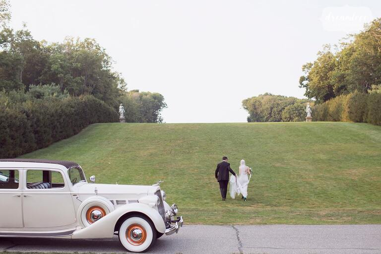 Bride and groom walk up the hill with their 1937 antique Packard coupe on the great lawn at the Crane Estate.