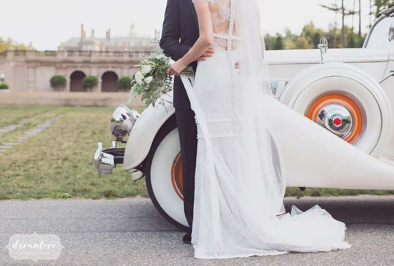 Bride in Vera Wang and groom lean against their antique packard car in front of the epic Great House on Castle Hill wedding venue.