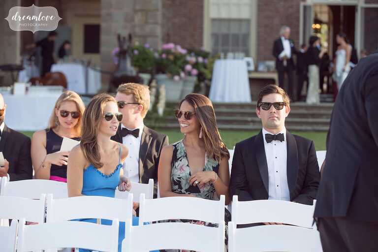 Candid wedding photography of guests waiting for outdoor ceremony.