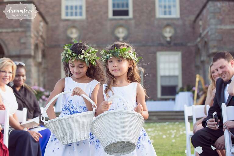 The flower girls walk down the aisle during the outdoor ceremony at the Crane Estate.