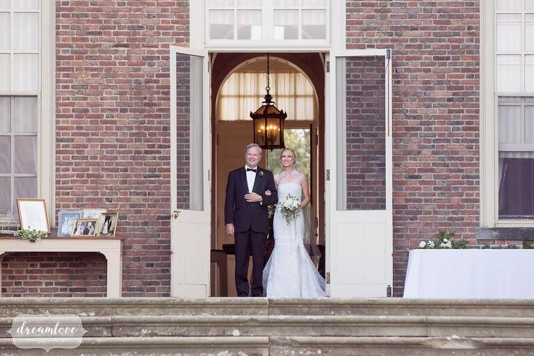 Bride and her father walk out of the Crane Estate mansion for the outdoor ceremony.