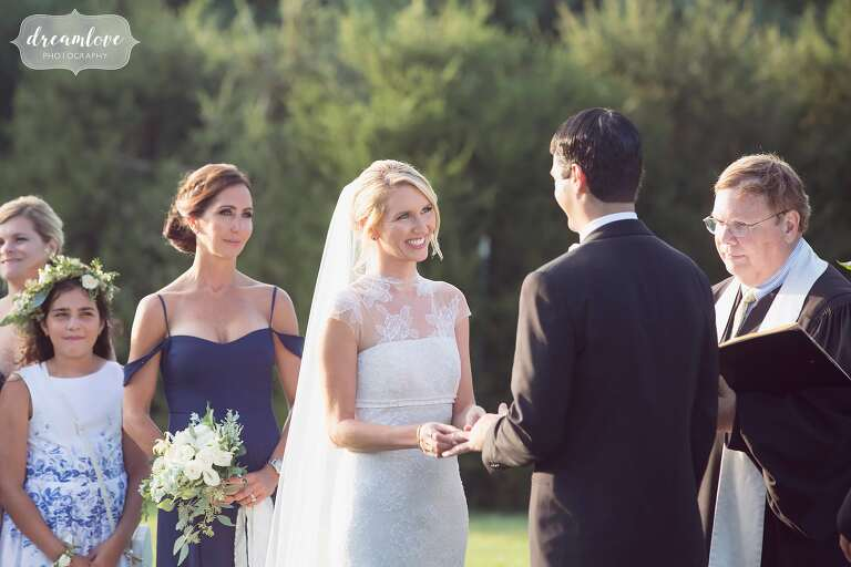 Beautiful and natural wedding photo of the bride looking at the groom during the ceremony at the Crane Estate.