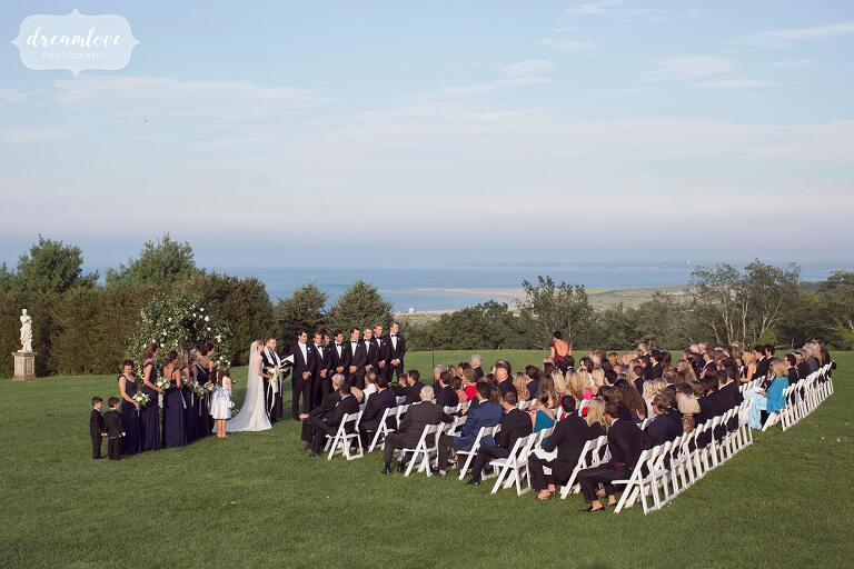 Coastal wedding ceremony outside overlooking the ocean at the Crane Estate in MA.