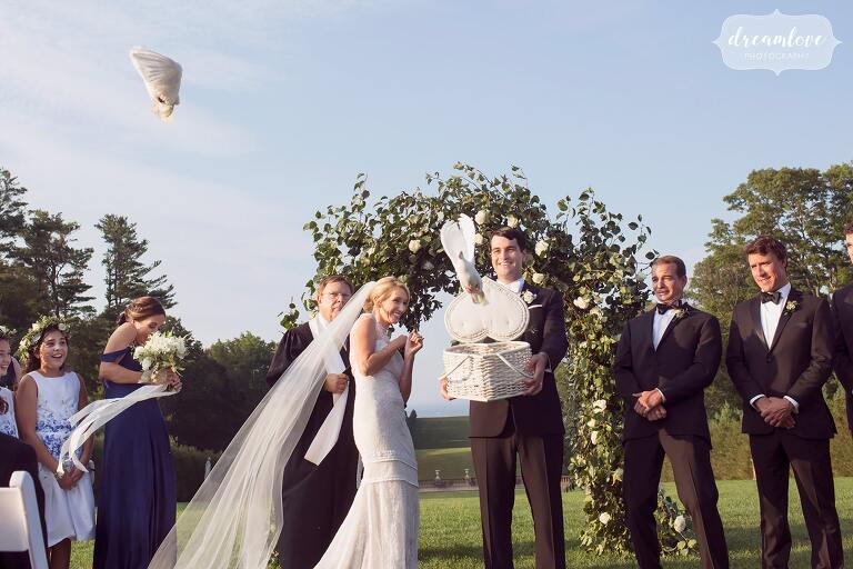 White doves fly out of a box during the wedding ceremony at the Crane Estate.
