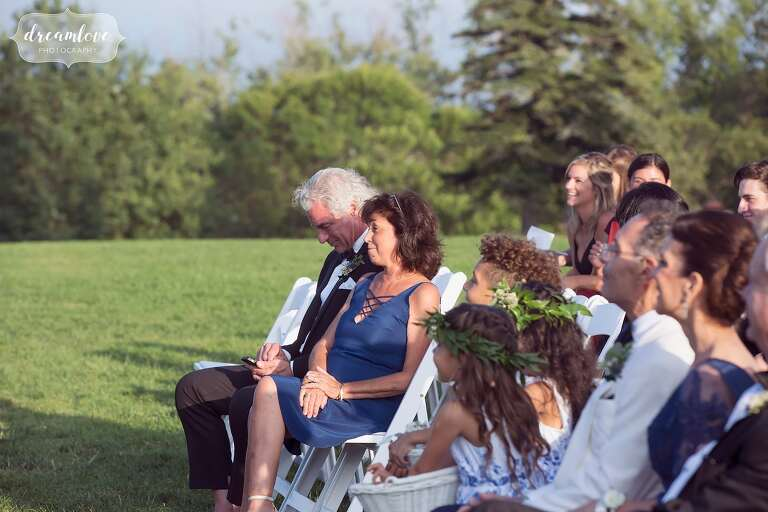 Parents watch the wedding ceremony on the lawn at the Castle Hill in MA.