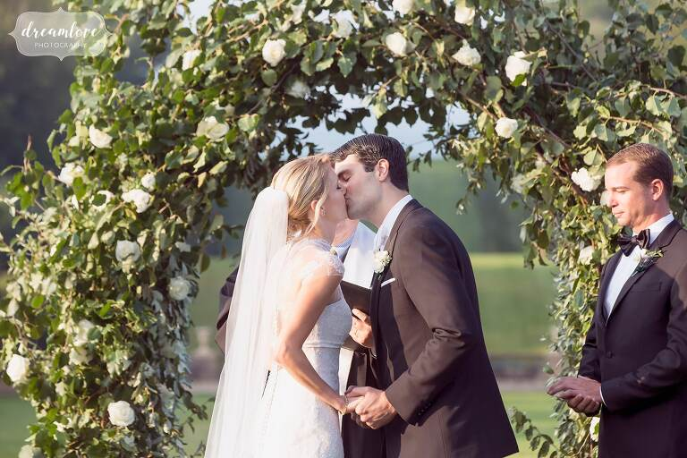 Bride and groom kiss during the wedding ceremony at the Crane Estate.