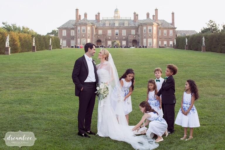 Funny candid photo of the bride and groom surrounded by kids at the Crane Estate house.