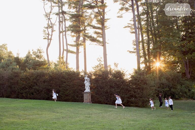 Kids run up the hill during sunset at the Crane Estate wedding in August.