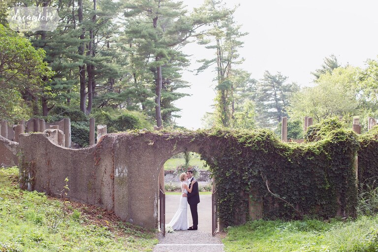 Bride and groom stand under an ivy covered arbor in the Italian Garden for natural portraits.