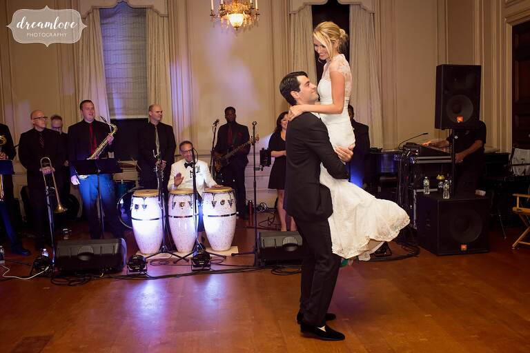 The groom lifts up the bride during their first dance in the ballroom at the Crane Estate.